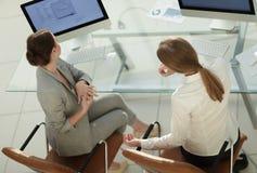 Ansicht von der Spitzenrückseite Geschäftsfrau, die mit einem Kollegen sitzt nahe dem Desktop spricht lizenzfreies stockbild