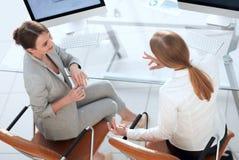 Ansicht von der Spitzenrückseite Geschäftsfrau, die mit einem Kollegen sitzt nahe dem Desktop spricht stockbild