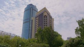 Ansicht von der Unterseite von schönen modernen Wolkenkratzern über den Bäumen herein bedeckt durch grüne Blätter gegen blauen be stock footage