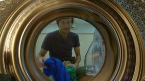 Ansicht von der Waschmaschine, wie ein junger Mann schmutzige Kleidung in sie setzt stock footage