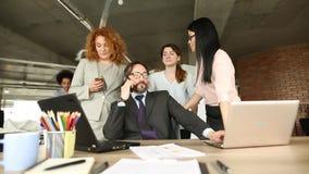 Ansicht von Direktor sitzend am Stuhl, Angestellte, die hinter ihm stehen stock video footage