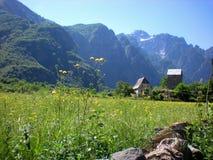 Ansicht von Dorfhäusern in Theth mit den albanischen Alpen im Hintergrund stockfotografie