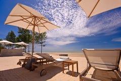 Ansicht von drei Stühlen und von Regenschirm auf dem Strand Stockbild