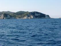 Ansicht von einem Boot auf der felsigen Küste von Antipaxos in Griechenland lizenzfreie stockfotos
