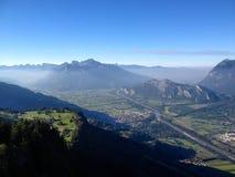 Ansicht von einer hohen alpinen Bergspitze in der Schweiz mit einer großen Ansicht der Täler und der Dörfer unten und der dunstig stockfotos