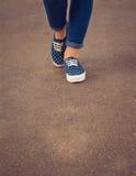 Ansicht von Füßen in den Turnschuhen und in den Jeans Lizenzfreies Stockfoto
