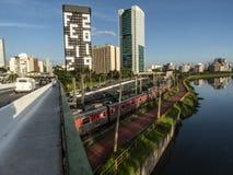 Ansicht von Gebäuden, VON CPTM-Zug, von Verkehr von Fahrzeugen und von Fluss in der begrenzten Pinheiros-Fluss-Allee lizenzfreie stockfotos