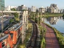 Ansicht von Gebäuden, VON CPTM-Zug, von Verkehr von Fahrzeugen und von Fluss in der begrenzten Pinheiros-Fluss-Allee stockbilder