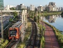 Ansicht von Gebäuden, VON CPTM-Zug, von Verkehr von Fahrzeugen und von Fluss in der begrenzten Pinheiros-Fluss-Allee stockfotografie