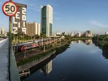 Ansicht von Gebäuden, VON CPTM-Zug, von Verkehr von Fahrzeugen und von Fluss in der begrenzten Pinheiros-Fluss-Allee stockbild