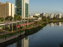 Ansicht von Gebäuden, VON CPTM-Zug, von Verkehr von Fahrzeugen und von Fluss in der begrenzten Pinheiros-Fluss-Allee stockfoto