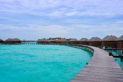Ansicht von hölzernen Weg- und Wasserlandhäusern auf Türkisozean der Cocos Bodu Hithi nehmen in Malediven mit Himmel mit schönen  stockfotos