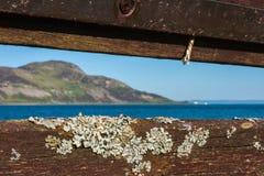 Ansicht von Insel durch alte Bank mit Flechte Heilige Insel, Lamlash Stockfotos