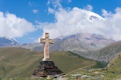 Ansicht von Kazbeg-Berg und von Kreuz, durch die Dreiheitskirche, Georgia Lizenzfreies Stockbild