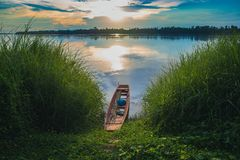 Ansicht von mae khong Fluss mit hölzernem Boot auf Wasser und grünem Busch Lizenzfreies Stockfoto