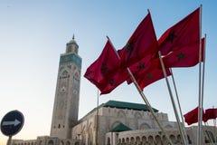 Ansicht von Moschee Hassan II und wellenartig bewegende marokkanische Flaggen Stockbilder
