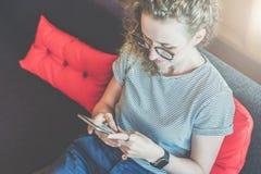 Ansicht von oben Junge Frau in den Gläsern und in einem gestreiften T-Shirt sitzt zu Hause auf der Couch und benutzt einen Smartp Stockfotografie