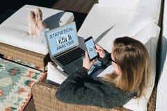 Ansicht von oben Junge Geschäftsfrau sitzt auf weißer Couch, unter Verwendung des Laptops mit Aufschriftanalyse auf Schirm Lizenzfreie Stockfotos