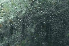 Ansicht von Regentropfen auf Fenster mit grünem, rotem und gelbem Farbbaum des Hintergrundes Autumn Abstract verwischte Hintergru stockfoto