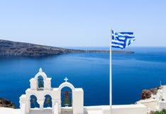 Ansicht von Santorini mit griechischem Flaggen- und Spitzendach der Kirche Stockfotografie