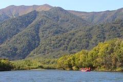Ansicht von schönem Gebirgsfluss mit Touristen auf orange Floss auf Wasser lizenzfreie stockfotografie