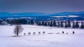Ansicht von schneebedeckten Bauernhoffeldern und von entfernten Bergen von lang Lizenzfreie Stockfotografie