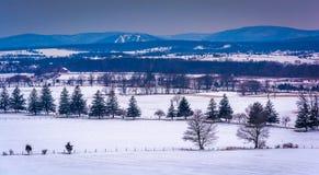 Ansicht von schneebedeckten Bauernhoffeldern und von entfernten Bergen von lang Lizenzfreie Stockbilder