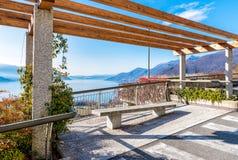 Ansicht von See Maggiore von der Terrasse mit Bank, Luino, Italien Lizenzfreie Stockfotografie