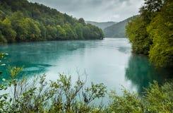 Ansicht von See mit Türkiswasser mit Bahnen des Regens fällt Stockfotografie