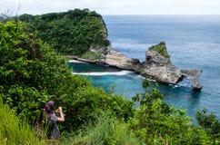 Ansicht von Spitze zu Atuh-Strand, Nusa Penida Bali, Indonesien mit der Person, die ein Foto der Bucht macht Lizenzfreie Stockbilder