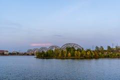 Ansicht von Stadtbild mit Eisenbahnbrücke in Riga, Lettland, auf blauer Stunde, Dämmerung mit einem freien Raum für Text, Konzept lizenzfreies stockbild
