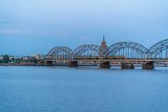 Ansicht von Stadtbild mit Eisenbahnbrücke und Zug auf ihm in Riga, Lettland, auf blauer Stunde, Dämmerung mit einem freien Raum f lizenzfreie stockbilder