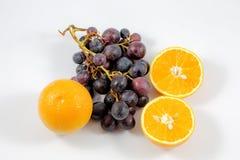 Ansicht von Trauben und von Orangen in einem weißen Hintergrund/in den Früchten/in Orange/in frischem/in den Trauben lizenzfreie stockbilder