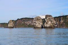 Ansicht von Tri Brata mit der Spitze Koryaksky-Vulkans im Hintergrund lizenzfreie stockfotografie