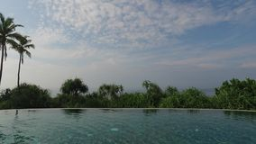 Ansicht von Unendlichkeitsrandpool zu Ozean und Palmen stock footage