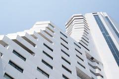Ansicht von unten über den weißen Wolkenkratzer mit Wohnwohnungen Lizenzfreies Stockbild