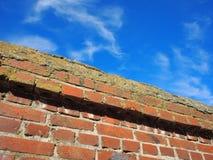 Ansicht von unten über ein Fragment des Zauns des roten Backsteins Stockfoto