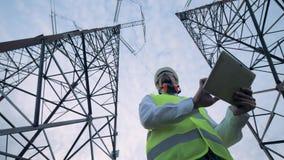 Ansicht von unten eines männlichen Ingenieurs, der eine Tablette zwischen ETL-Bau betreibt stock footage