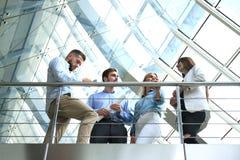 Ansicht von unten Moderne Leute in der Freizeitkleidung, die eine Geistesblitzsitzung bei der Stellung im kreativen Büro hat lizenzfreie stockfotografie