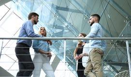 Ansicht von unten Moderne Leute in der Freizeitkleidung, die eine Geistesblitzsitzung bei der Stellung im kreativen Büro hat stockfoto