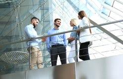Ansicht von unten Moderne Leute in der Freizeitkleidung, die eine Geistesblitzsitzung bei der Stellung im kreativen Büro hat lizenzfreie stockbilder