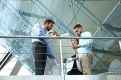 Ansicht von unten Moderne Leute in der Freizeitkleidung, die eine Geistesblitzsitzung bei der Stellung im kreativen Büro hat stockfotografie