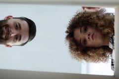 Ansicht von unterhalb eines jungen Paares, das innerhalb des Kastens schaut Lizenzfreies Stockfoto