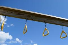 Ansicht von unterhalb von den gelben Kletterstange-Ringen, die vom hölzernen Strahl auf Spielplatz hängen Stockfotos