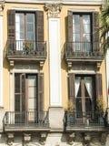 Ansicht von vier Fenstern mit balconys auf einem Wandhintergrund lizenzfreie stockbilder