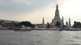 Ansicht von Wat Arun-Tempel mit Booten und von Chao Phraya im Sonnenuntergang stock video footage