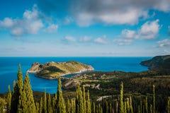 Ansicht zu Assos-Dorf im Sonnenlicht und im schönen blauen Meer Grüne Zypressenbäume im Vordergrund Kefalonia-Insel, Griechenland lizenzfreie stockfotos