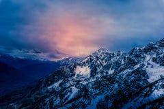 Ansicht zu den schneebedeckten Bergen mit einem drastischen bewölkten Himmel lizenzfreie stockfotografie