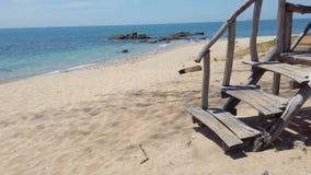 Ansicht, zum des Strandes mit Felsen auf Tropeninsel und hölzernem Treppenhaus zum Bungalow zu versanden stock video