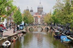 Ansicht zum Kanal mit der Basilika von Sankt Nikolaus am Hintergrund in Amsterdam, die Niederlande Lizenzfreie Stockfotos